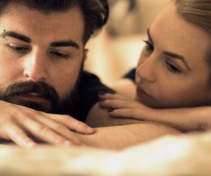 Unhappy young heterosexual couple in bedroom