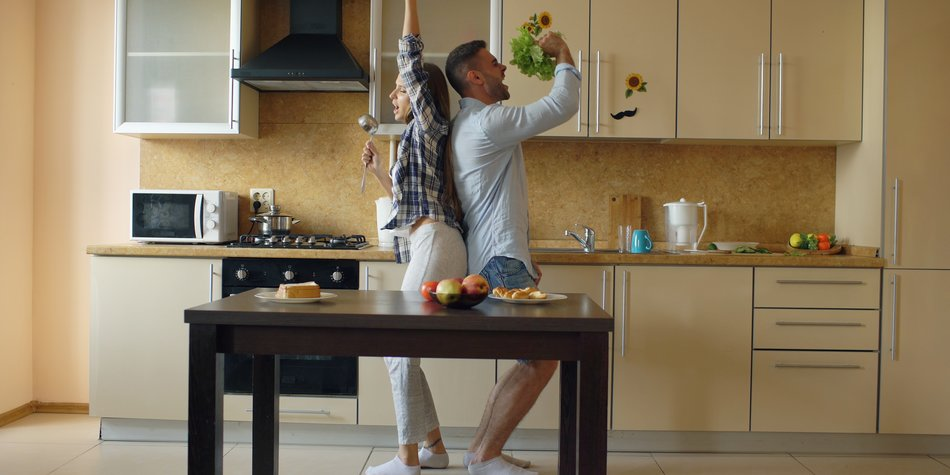 Attractive young joyful couple have fun dancing and singing while cooking in the kitchen at home in the morining