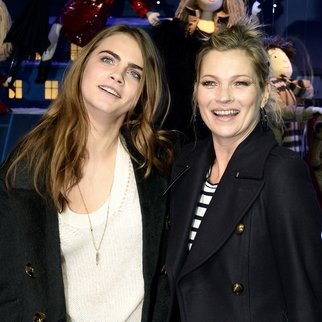 """British models Kate Moss (R) and Cara Delevingne pose during the launching of the Paris' department store """"Printemps Haussmann"""" Christmas decorations on November 6, 2014 in Paris. AFP PHOTO / FRANCK FIFE (Photo credit should read FRANCK FIFE/AFP/Getty Images)"""