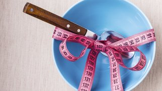 Dieting healthy lifestyle and slim body concept. Pink measuring tape around empty blue bowl on table with spoon, top view