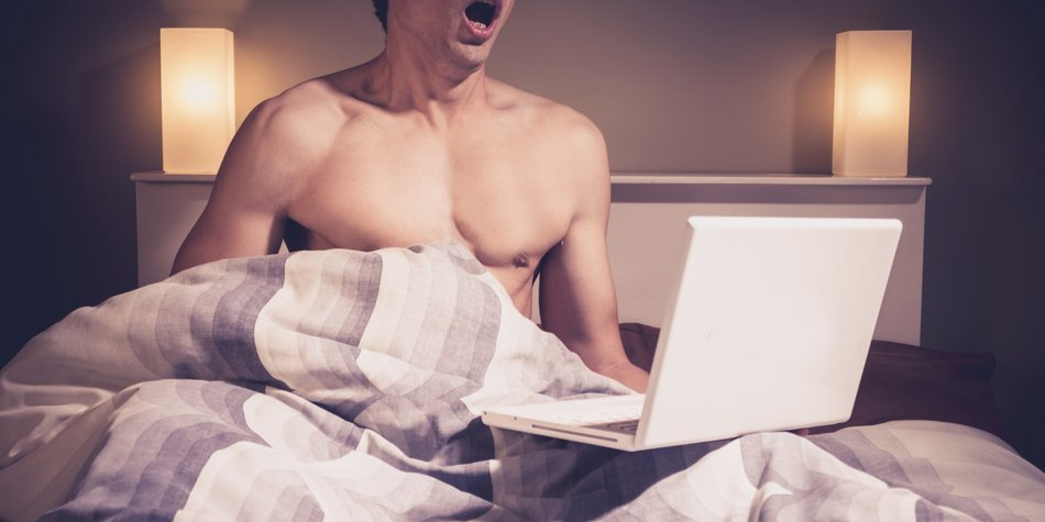 Young man is sitting in bed and watching pornography on his laptop