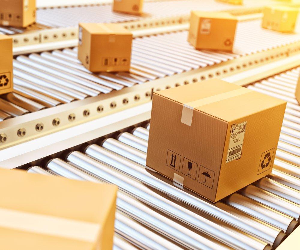 Cardboard boxes on conveyor belt in warehouse