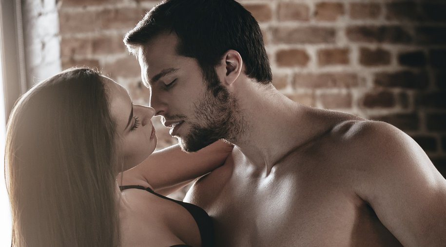 Handsome young shirtless man carrying his girlfriend and kissing her while standing against brick wall