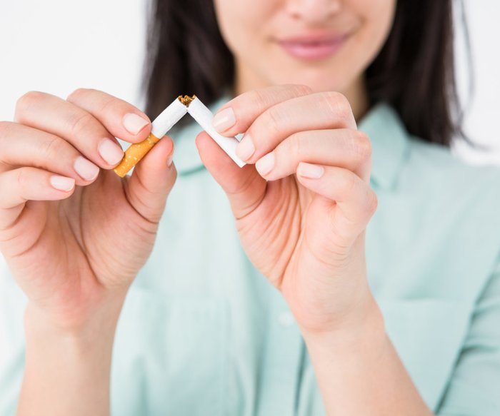 Smiling woman snapping cigarette in half on white background
