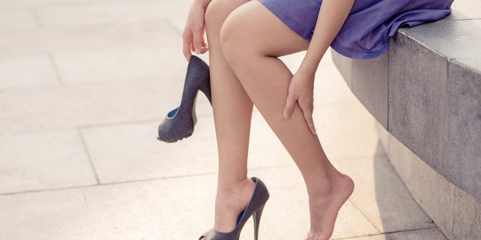 Cropped image of woman in high heels massaging her tired legs