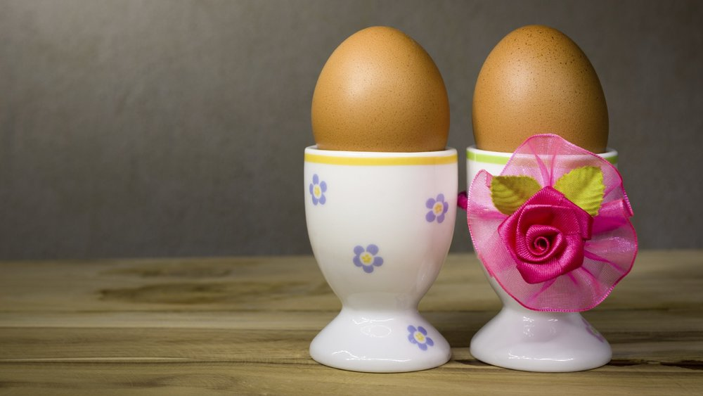 Eggcup and boiled egg couple on wooden table in love feel.