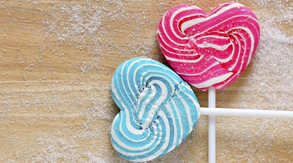 Colourful lollipop in shape of heart on wood background