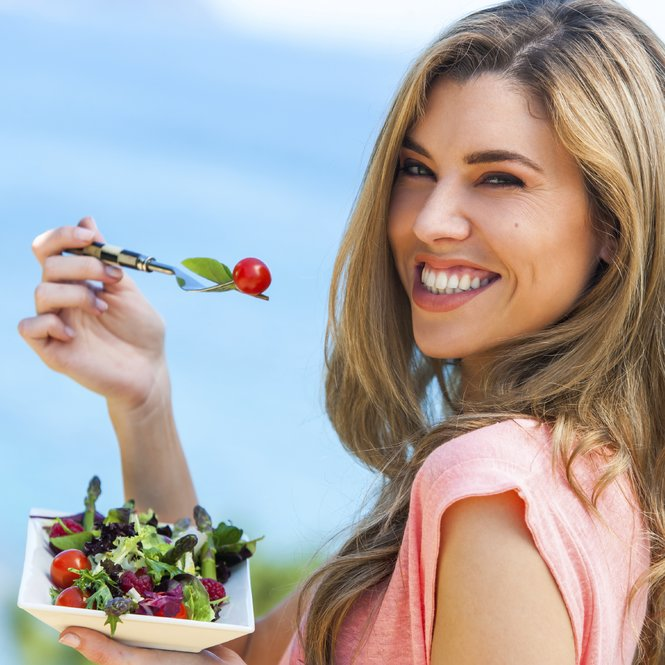 Portrait of beautiful young woman holding green salad outdoors at seaside.