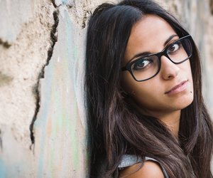 Beautiful brunette woman with sunglasses over a ruinous wall