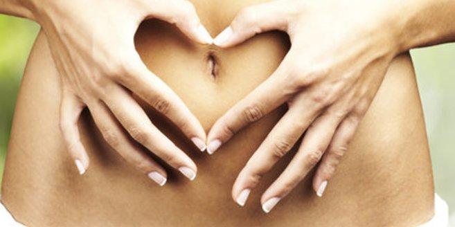 Frau legt die Hände über ihen Bauch
