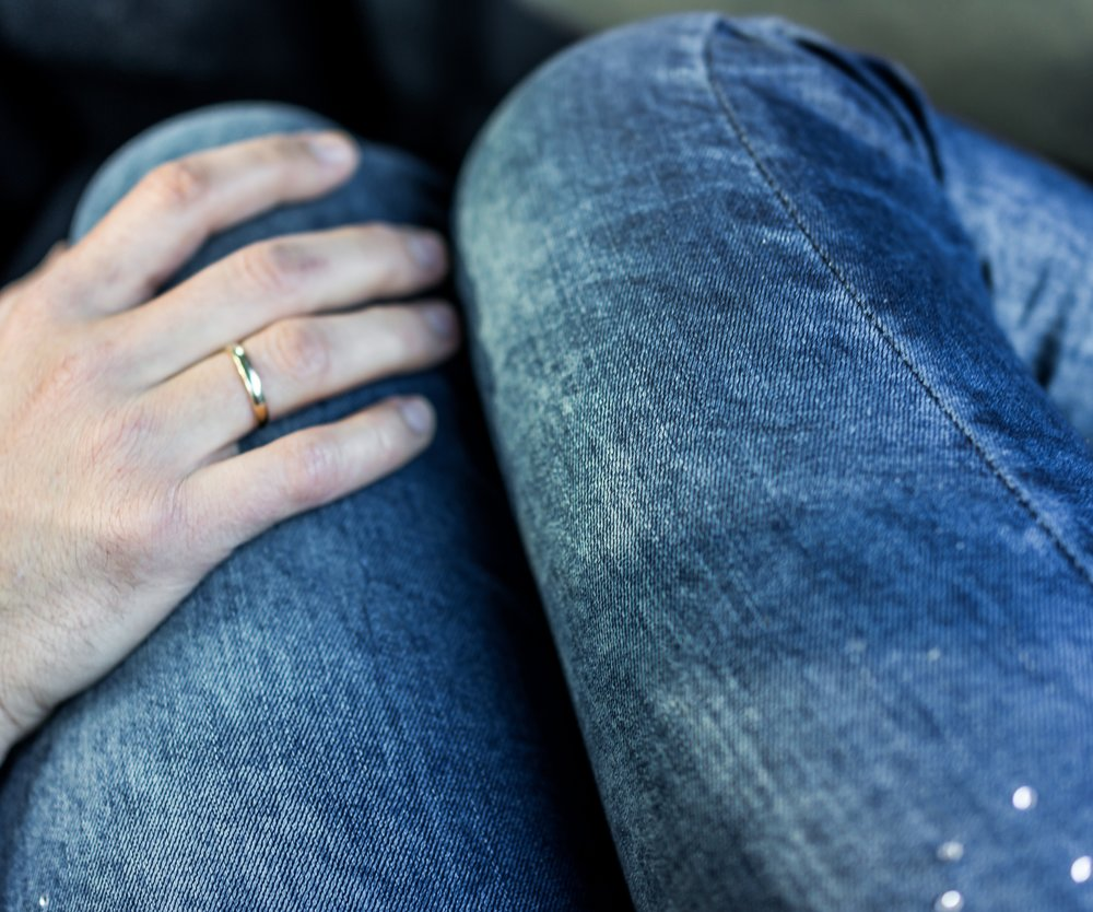 Man's hand with wedding ring on woman's legs in jeans in car