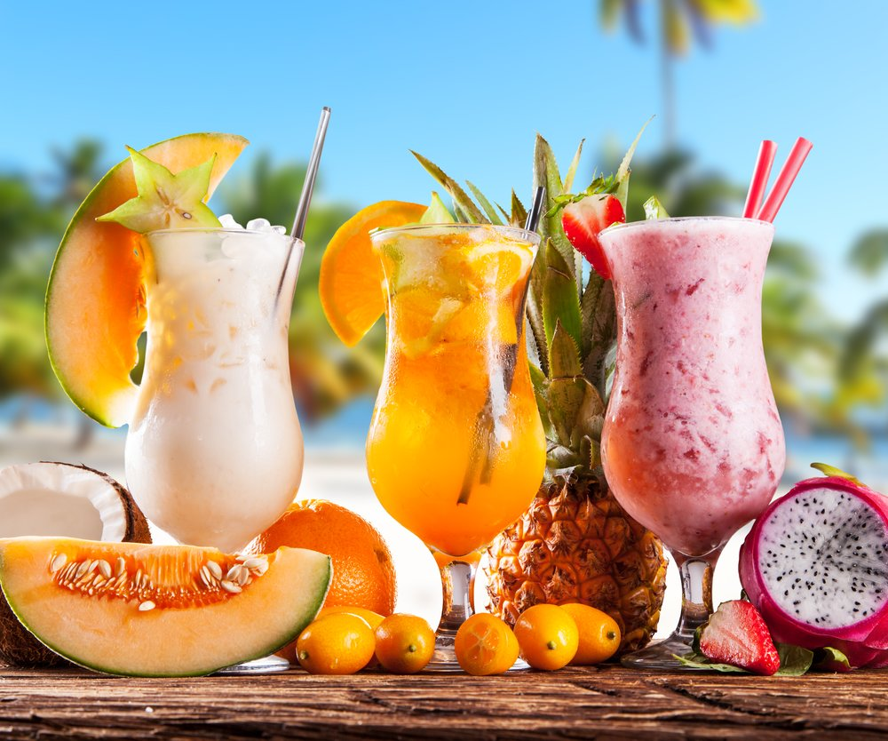 Exotic summer drinks served on wood. Blur sandy beach as background
