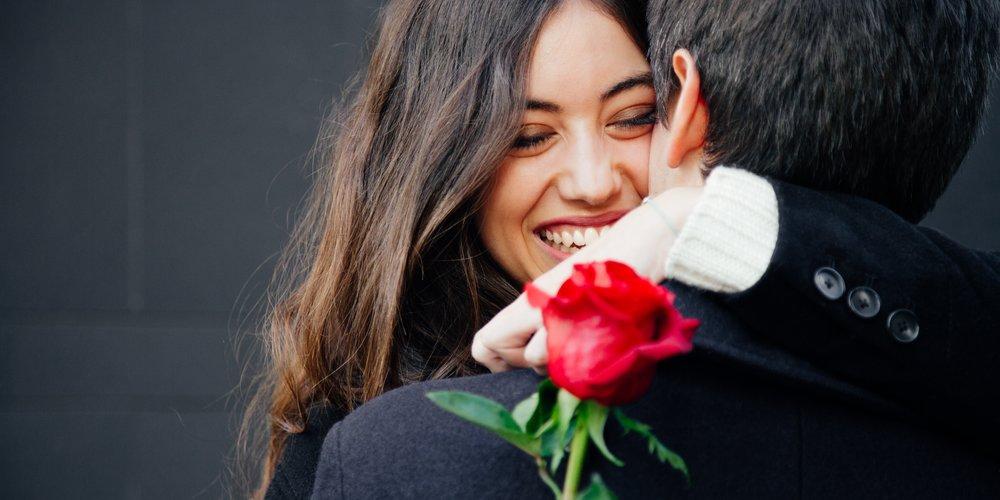 Frau umarmt ihren Freund mit einer Rose in der Hand