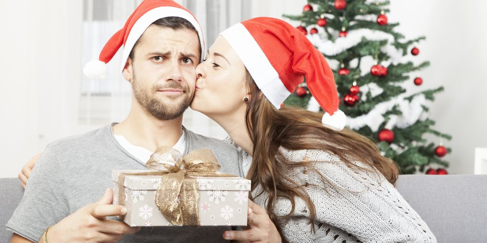man is sceptical about christmas gift while his girlfriend give him a kiss