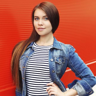 Portrait of beautiful young woman in jeans jacket against the red wall