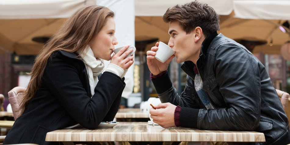Side view of young couple drinking coffee together at outdoor restaurant