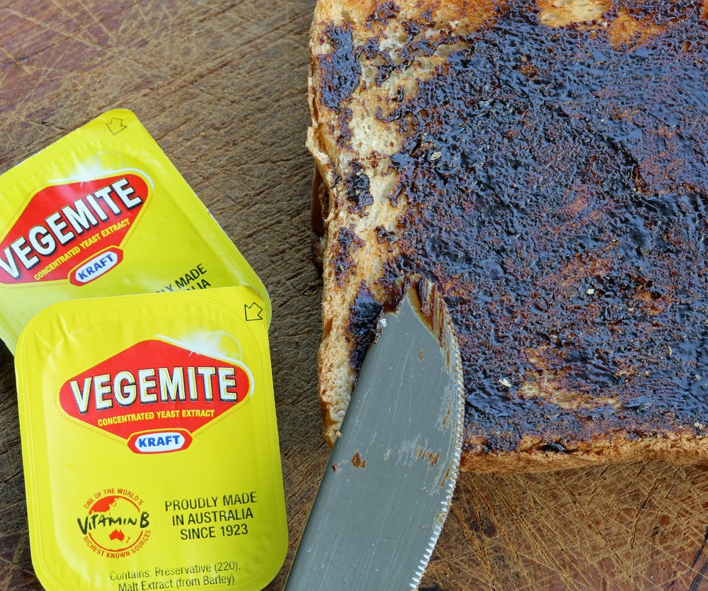 Reichenbach, Germany - 0ctober 4, 2013: Vegemite on Toast - Produce in Australia at Kraft Foods' Port Melbourne. It's a popular dark brown australian Food Paste - used as spread for sandwiches and toast - the Australian People love it for Breakfast. It taste similar to beef bouillon. I shot this photo at home in Germany - the Vegemite was a Souvenir from my Australia Trip. Toast with Knife and 2 small packages of Vegemite.