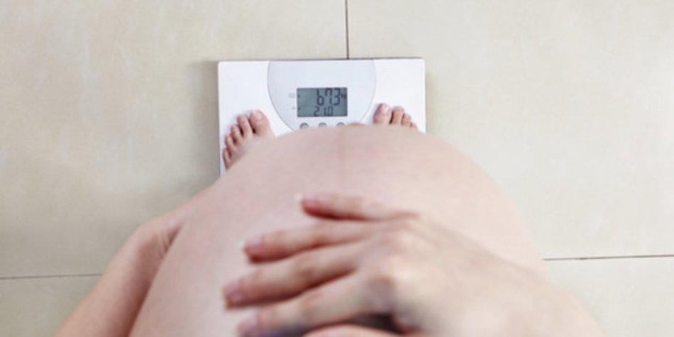 Abnehmen in der Schwangerschaft: Schwangere Frau auf Waage.