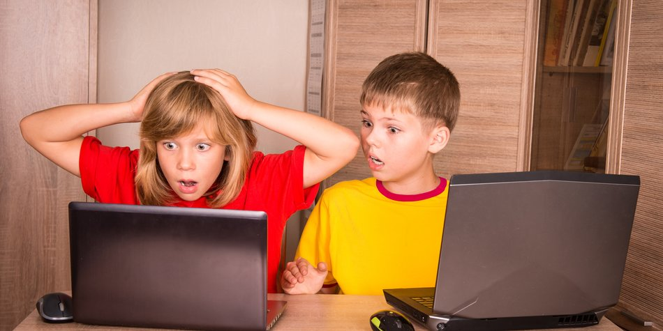 Girl having a computer problem. Cute children using laptops at home.