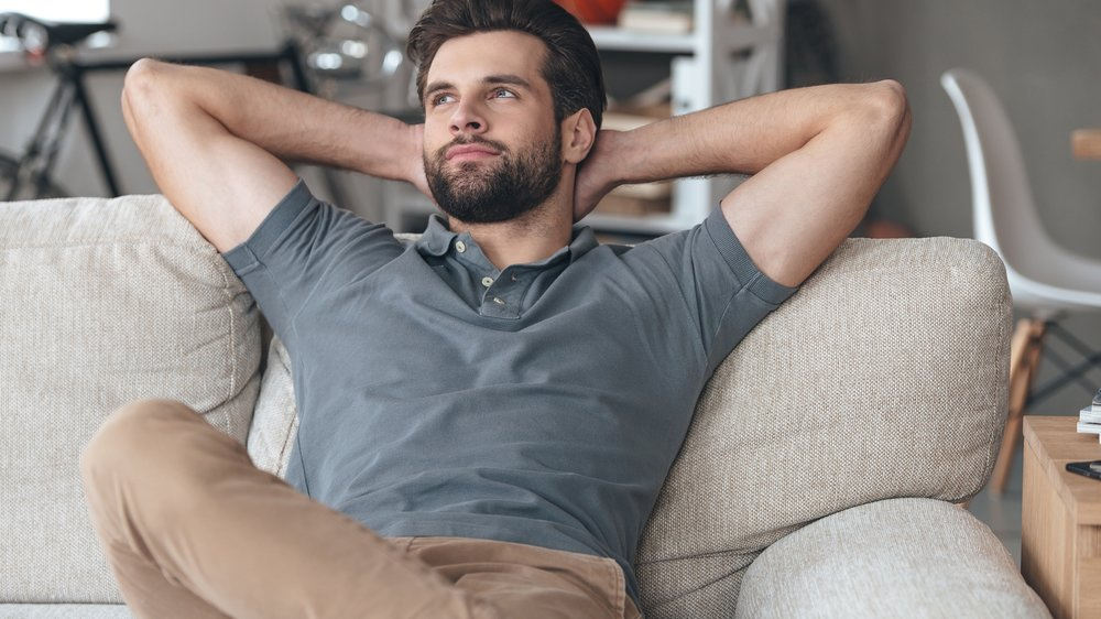 Handsome young man keeping hands behind his head and looking thoughtful while sitting on the couch at home
