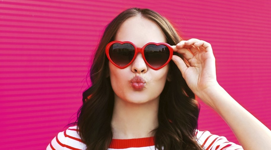 Portrait of pretty sweet woman in red sunglasses blowing lips having fun over pink background