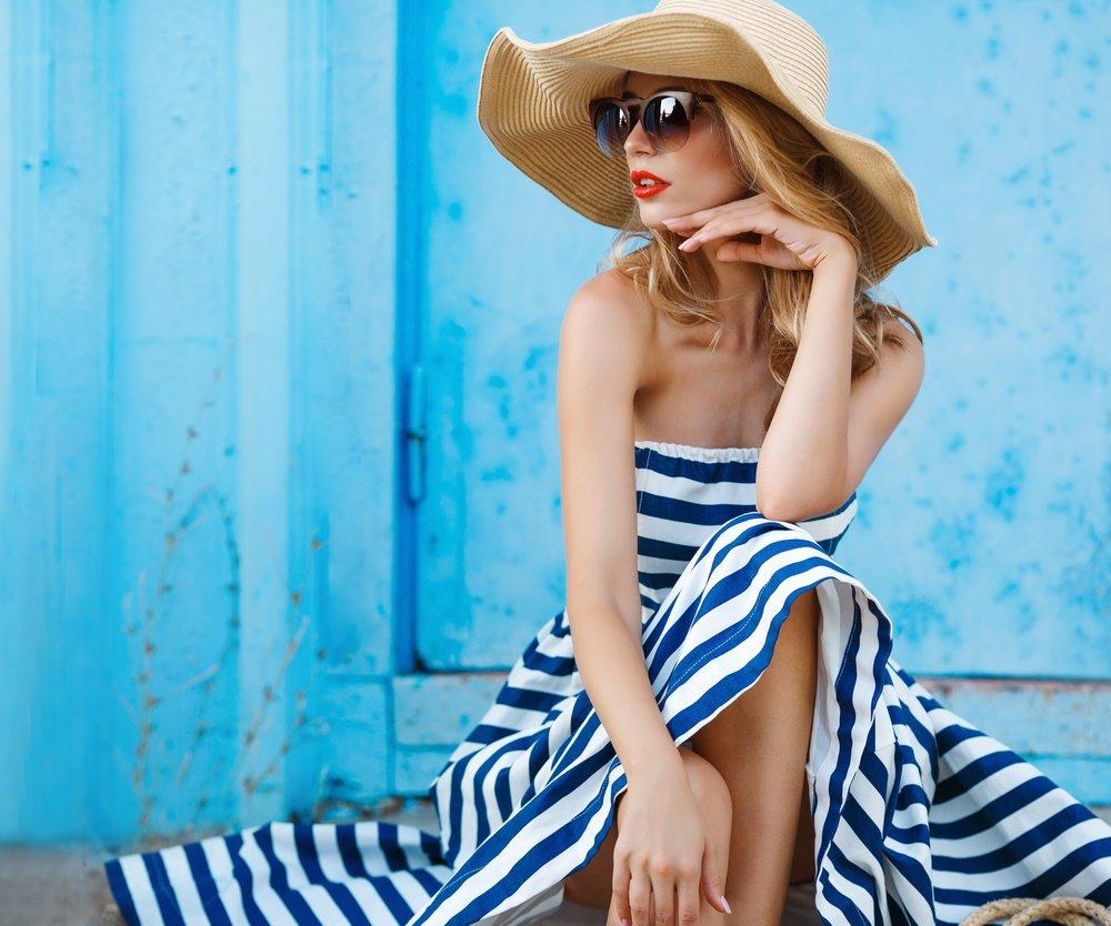 Frau in Streifenkleid mit Sonnenhut