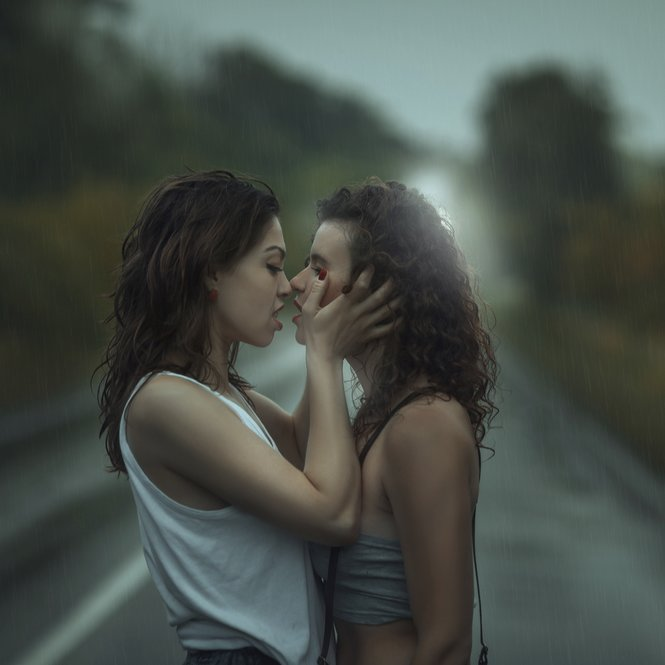 Girls kissing in the rain. They soaked.