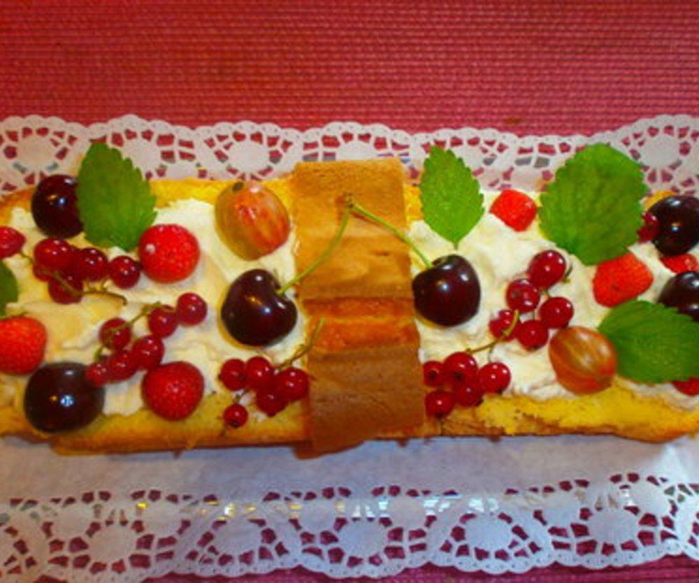 Obstkorb aus Biskuit gefüllt mit Früchten Und Schmandsahne