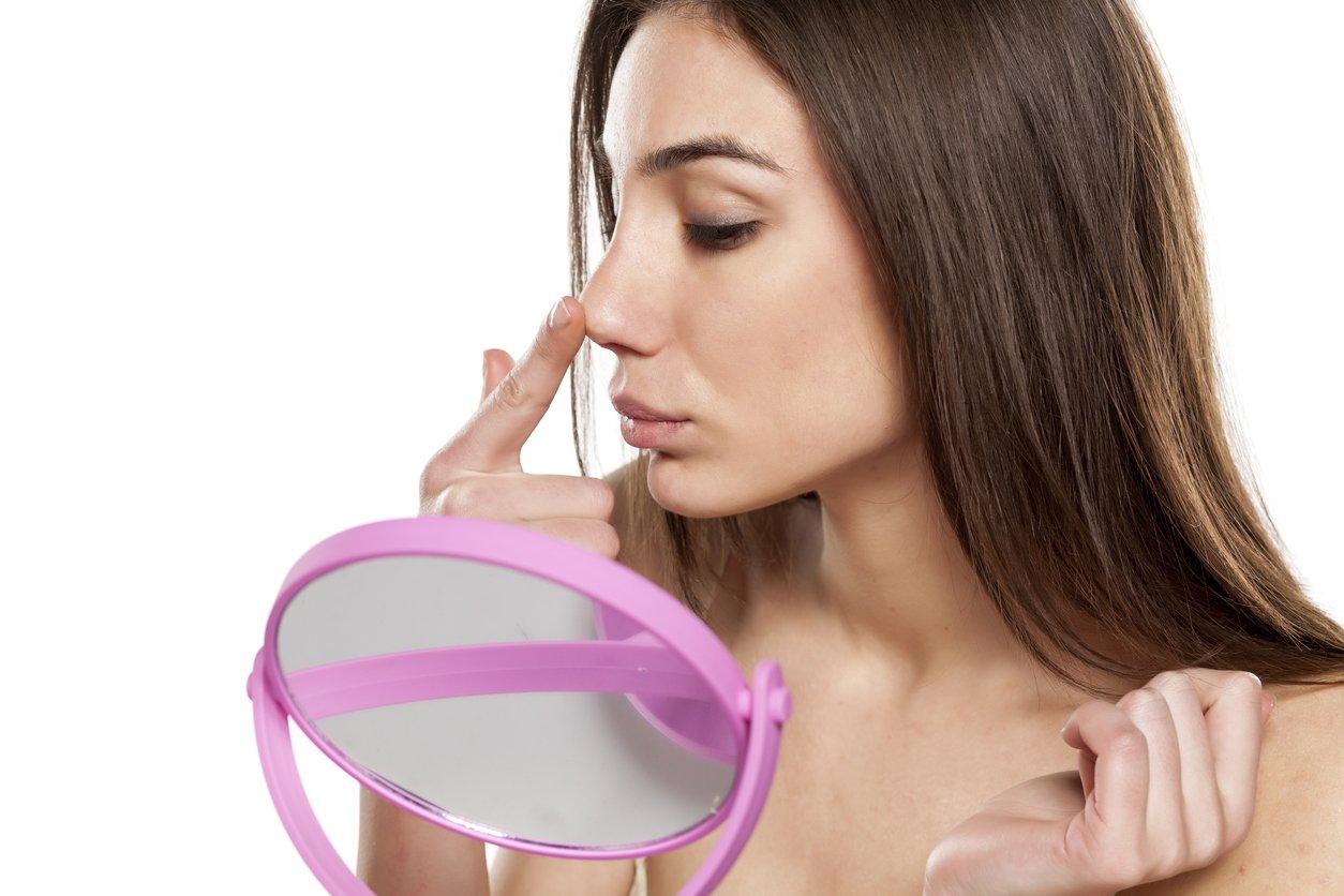 Nasenhaare entfernen: Frau am Spiegel