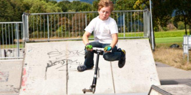 Kind mit Cityroller auf einer Halfpipe