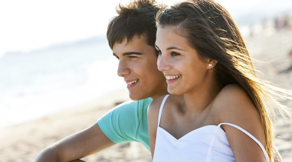 Cute teen couple sitting together on beach at sunset.
