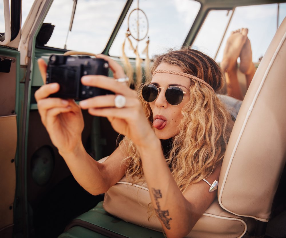 A Road trip shot of young blonde boho hipster girl taking a selfie in the front seat of retro van parked on a sandy beach