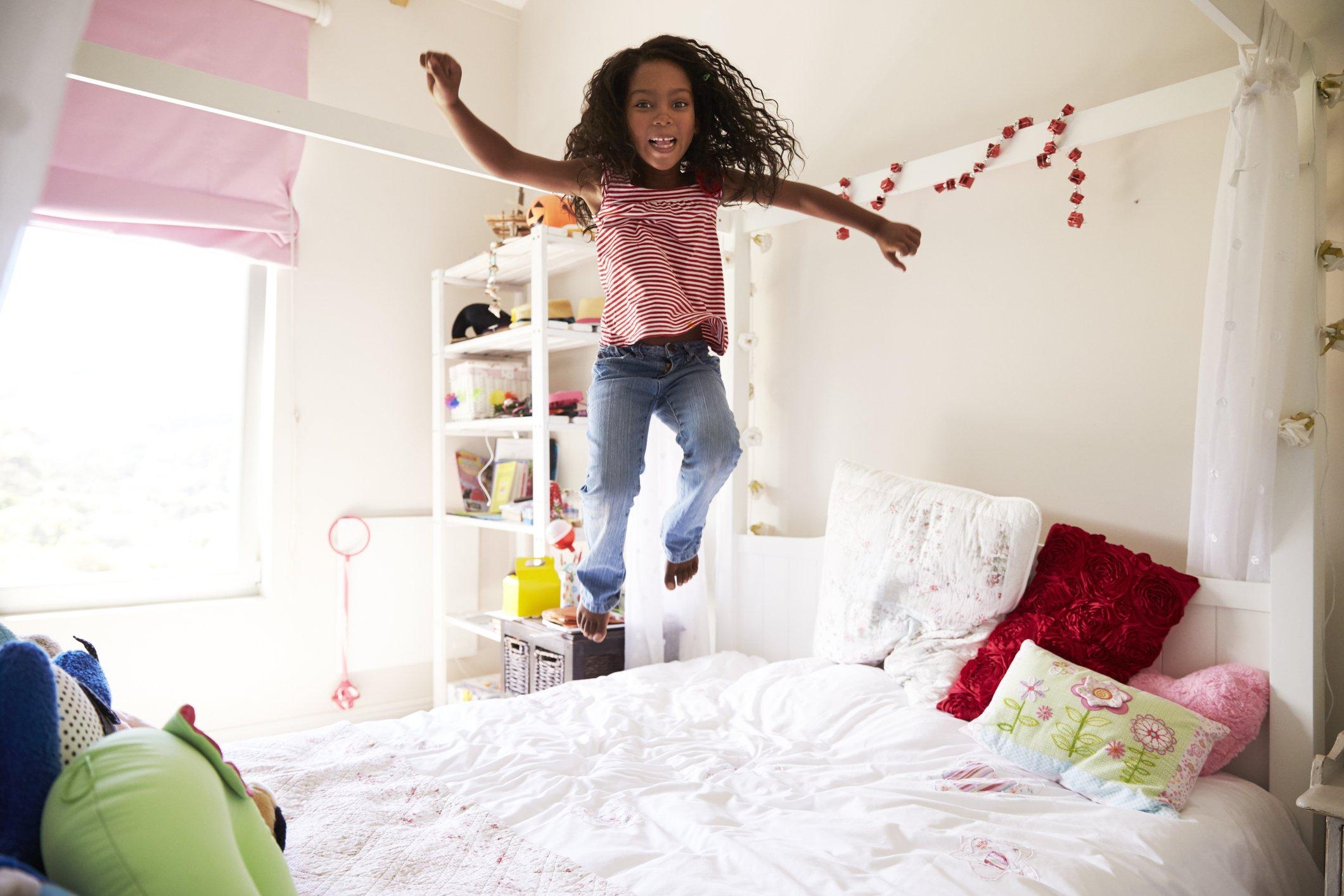 Mädchen hüpft auf ihrem Bett