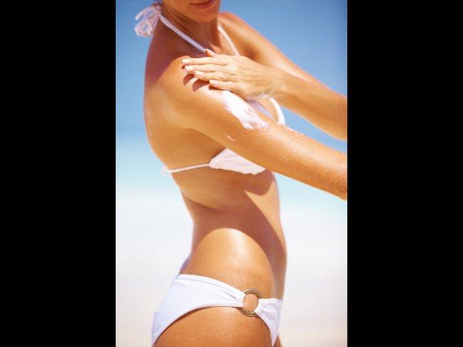 Frau trägt Sonnencreme auf