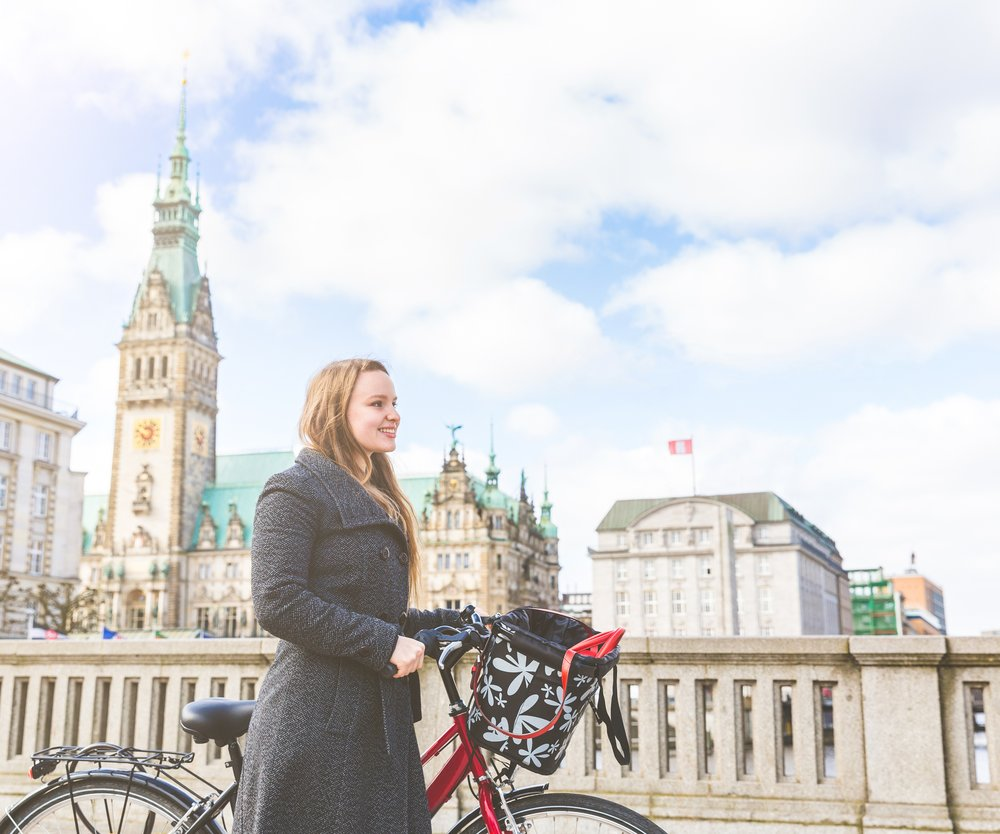 Young woman walking and holding a bike in Hamburg. Blonde girl in the city centre, walking and looking forward. She is wearing a warm coat. City hall in background.