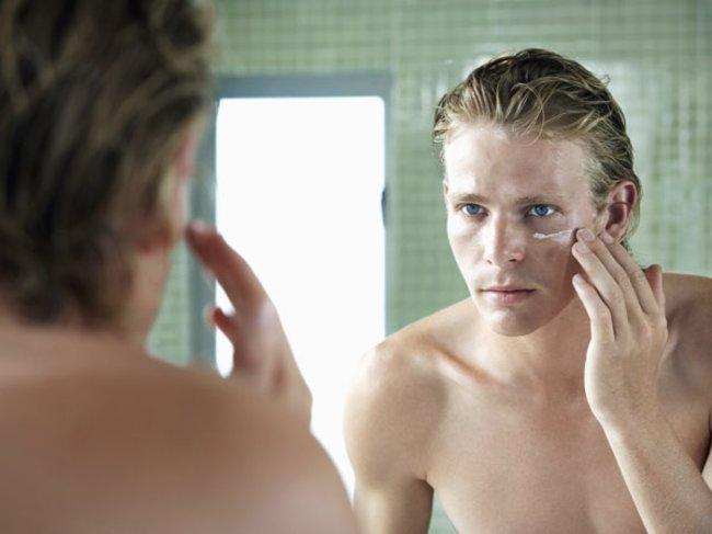 Mann mit Creme vorm Spiegel
