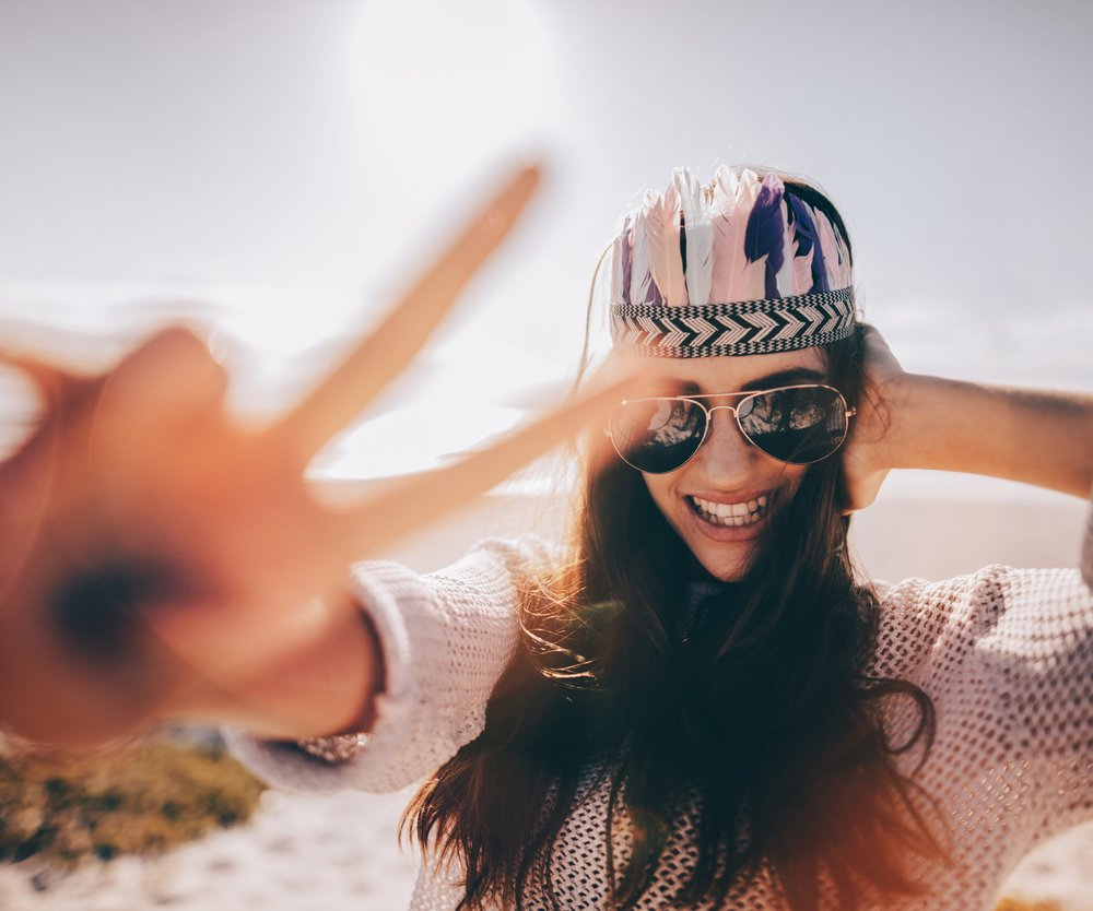 Close up hipster girl smiling and making peace sign with hand while standing on sunny sandy beach