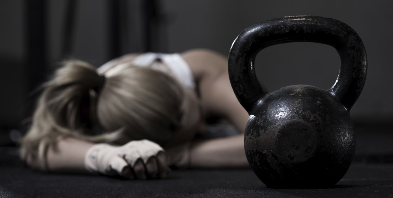 Portrait of drained girl after hard crossfit training with kettlebell