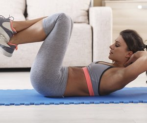 Attractive female doing exercise in her living room.She doing abs.