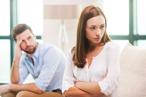 Depressed young woman keeping arms crossed and looking away while man sitting behind her on the couch