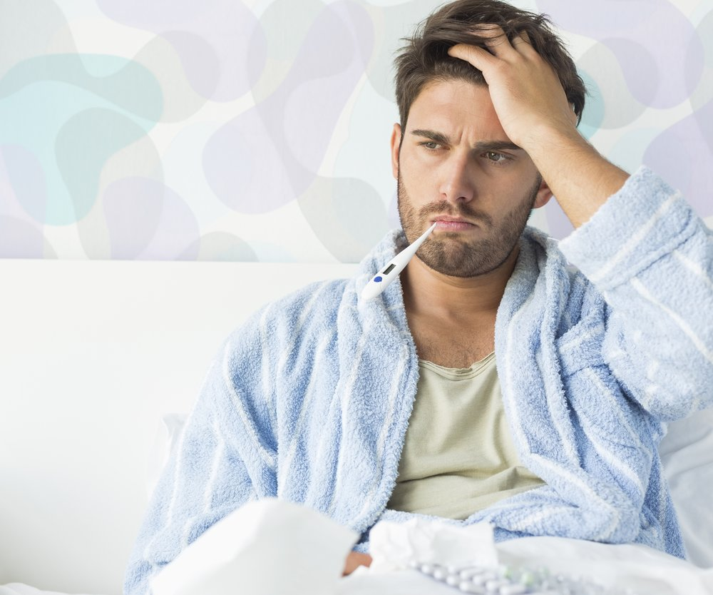 Sick man with thermometer in mouth sitting on bed at home