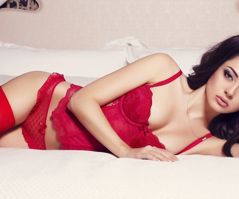 sexy brunette in red lingerie and pantyhose lying in the bed