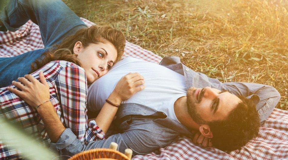 Paar liegt auf einer Picknickdecke