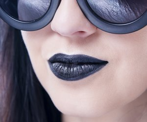 Beautiful woman fashion model portrait in sunglasses with black lips and earrings. Creative hairstyle and make up. Beauty girl close up on a gray background