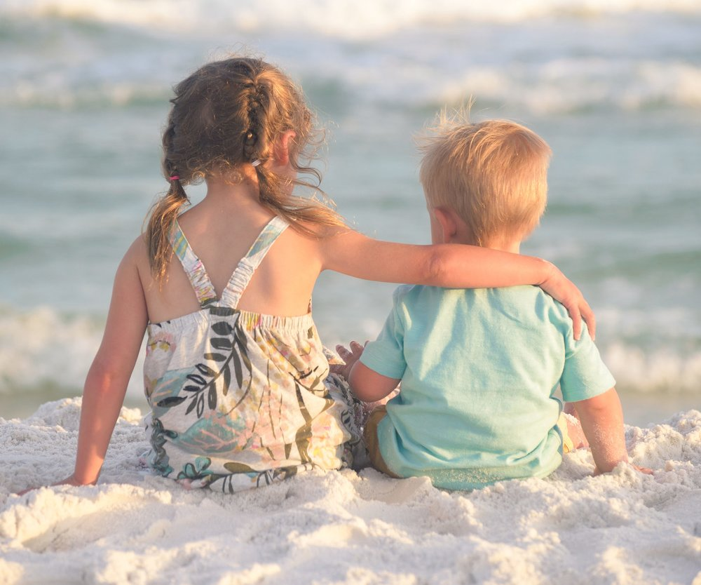 Brothers and sisters are friends for a lifetime. Spending time on the beach near the ocean, talking and hugging - it's the best time together!