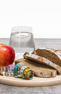 Healthy diet meal with apple, bread, tape measure and water on a round plate on a wooden floor with white background.