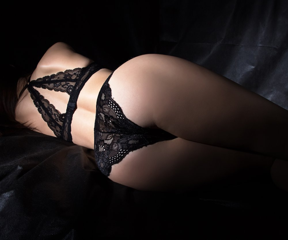 Photo of sexy woman's buttocks on black background