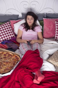 Frau isst Pizza im Bett