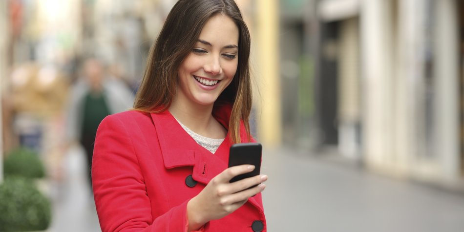 Girl walking and texting on the smart phone in the street wearing a red jacket in winter