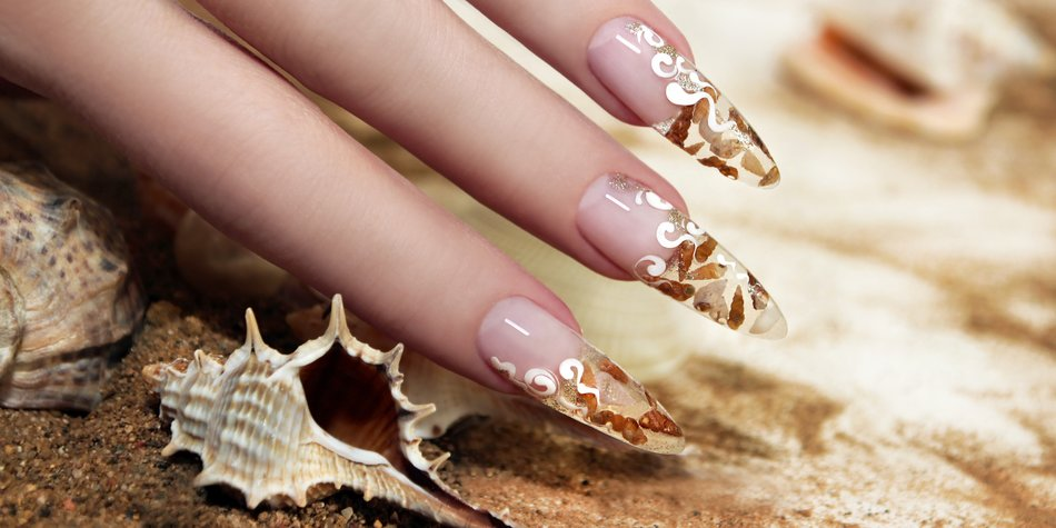 Nail design with brown and white these little shells inside gel nails on the background of shells and sand